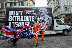 © Licensed to London News Pictures. 22/02/2020. LONDON, UK.  People carrying the US and UK flags in front of a van carrying a placard during a march from Australia House in Aldwych to Parliament Square in support of Wikileaks founder Julian Assange.  The full extradition trial of Mr Assange begins in London on 24 February.  Photo credit: Stephen Chung/LNP