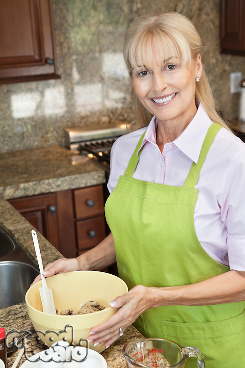 Portrait of a happy senior woman preparing food in kitchen
