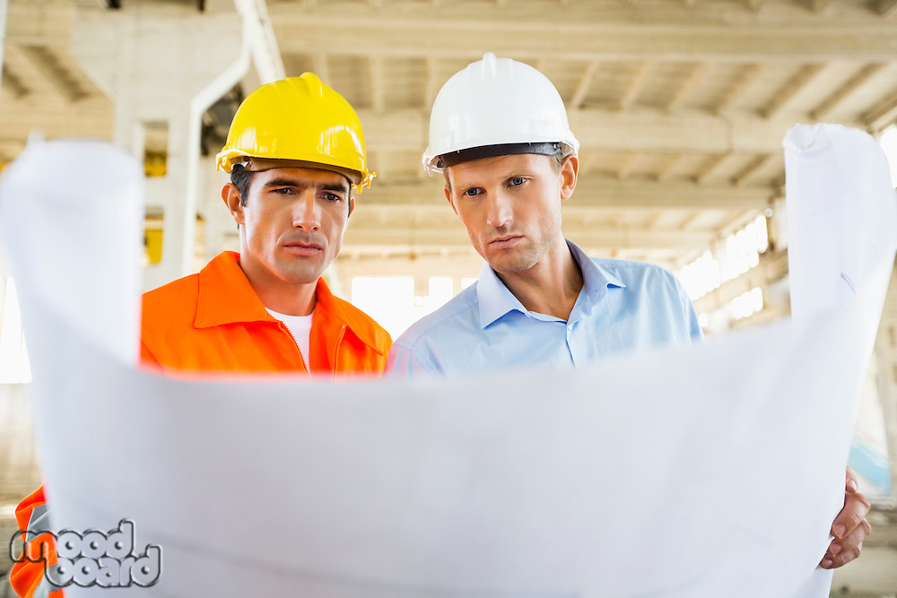 Male architects reviewing blueprint at construction site