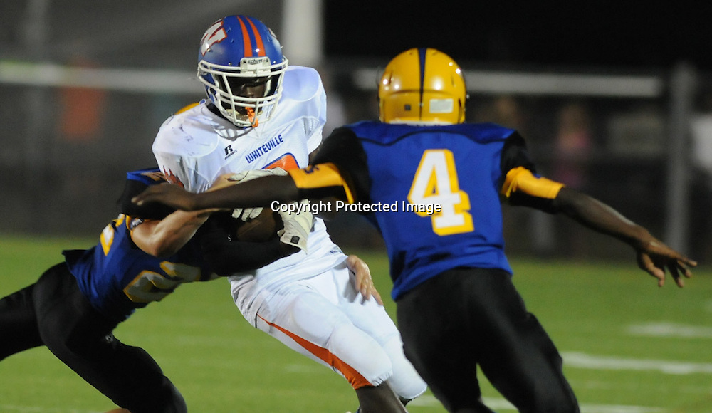 Whiteville's Imeek Watkins rushes against Laney's Raequan McAllister, back, and Garrett Wilson in the final game of the 28th Annual BB&T Football Jamboree Friday August 15, 2014 at Legion Stadium in Wilmington, N.C. (Jason A. Frizzelle)