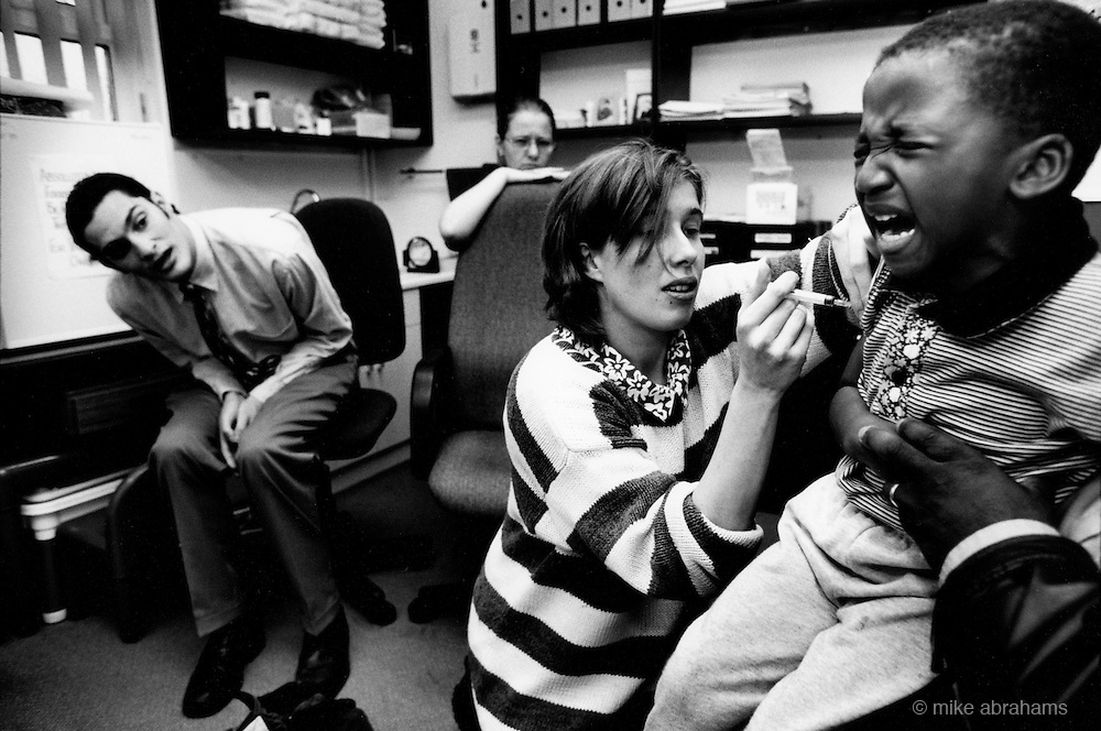 Child receiving vaccination at local health centre. Liverpool, 1999. England, United Kingdom