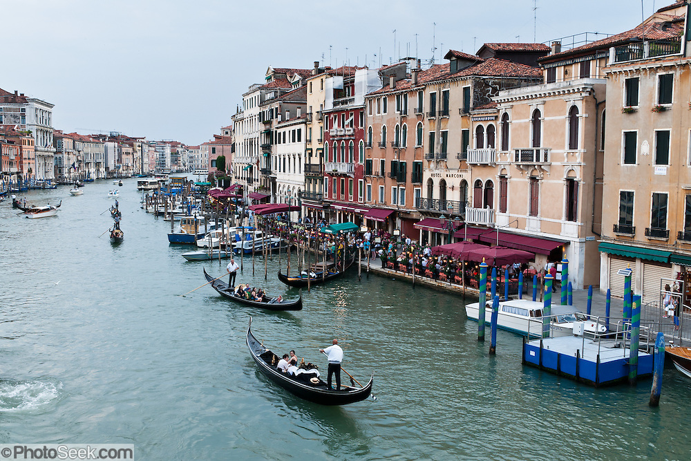 "Gondolas are traditional, flat-bottomed rowing boats which ferry people through Venetian canals. From a peak of 10,000 gondolas 200 years ago, just 500 gondolas now serve Venice. The banana-shaped modern gondola was developed in the 1800s. The left side of the gondola is made longer than the right side to resist leftwards drift at the forward stroke. The gondolier stands on the stern facing the bow and rows just on the right side, with a forward stroke and compensating backward stroke. The oar or rèmo is held in an oar lock, or fórcola, shaped for several rowing positions. The decorative fèrro (meaning iron) ornament on the front can be made of brass, stainless steel, or aluminum, as counterweight for the gondolier standing near the stern. The six horizontal lines and curved top of the ferro represent Venice's six sestieri (districts) and the Doge's cap. Painting gondolas black originated as a sumptuary law eliminating ostentatious competition between nobles. Until the early 1900s, many gondolas had a small cabin (felze) with windows which could be closed with louvered shutters--the original ""venetian blinds."" The romantic ""City of Canals"" stretches across 117 small islands in the marshy Venetian Lagoon along the Adriatic Sea in northeast Italy, Europe. Venice and the Venetian Lagoons are honored on UNESCO's World Heritage List."