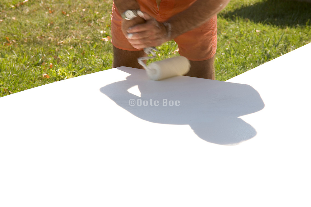 man painting white boards