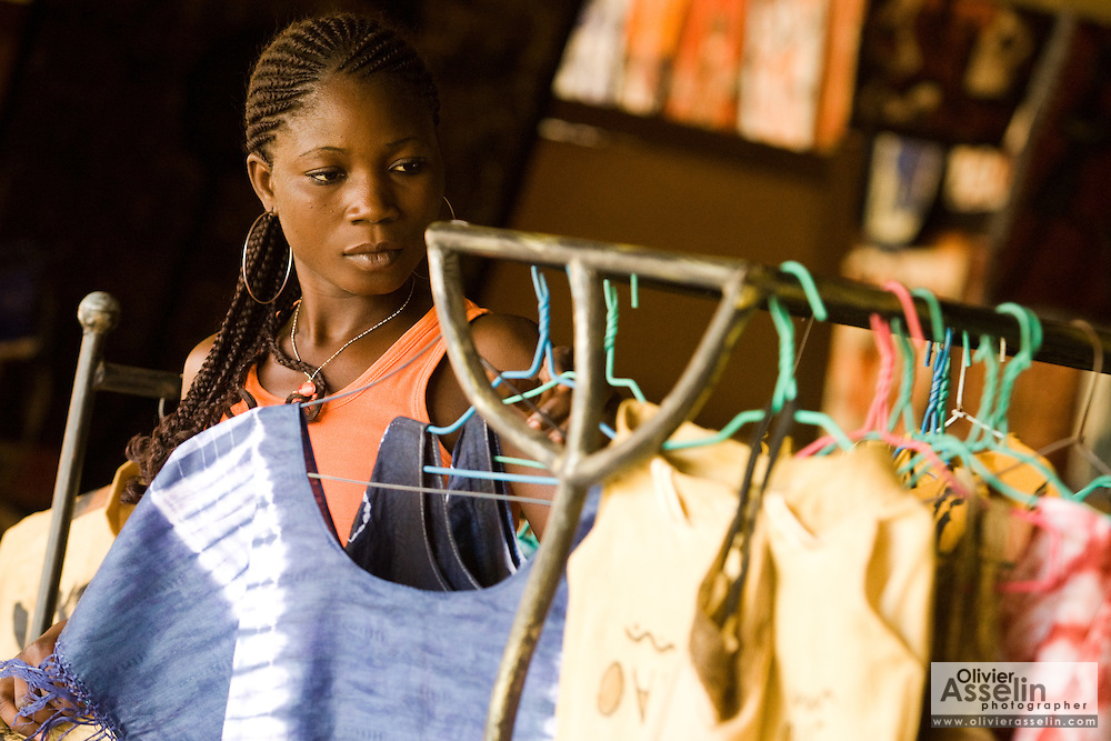 A vendor hangs clothes in her shop at the Village Artisanal de Ouagadougou, a cooperative that employs dozens of artisans who work in different mediums, in Ouagadougou, Burkina Faso, on Monday November 3, 2008.