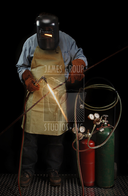 Person in protective welding gear heating a piece of metal