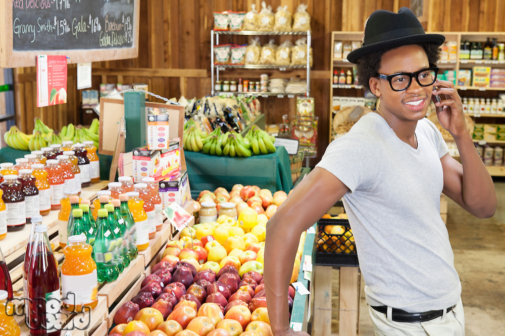 African American man using cell phone at supermarket
