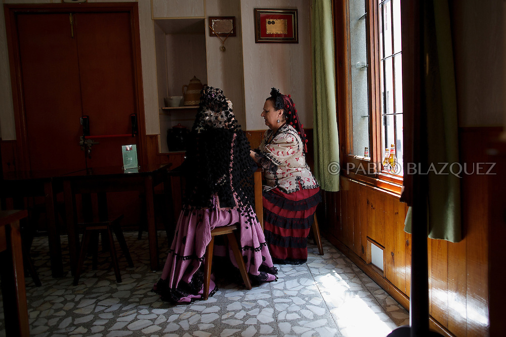 'Women sit in a bar as they cerebrate the 'La Maya' tradition in the streets around the San Lorenzo church on May 10, 2015 in Lavapies neighborhood, Madrid, Spain. 'La Maya' festivity is a pagan tradition to celebrate the beginning of the spring which is believed to come from the medieval age. In old times the 'Maya's Festival' used to take place at The 'Mayas' field' (Prado de las Mayas) which is where now the San Lorenzo church is located. La Maya combines symbols of fertility and prosperity on agriculture and shepherding economy. A 'Maya' girl dressed with traditional customs sits on an altar in the street decorated with flowers, plants and cushions. Other Mayas and Mayos offer flowers, traditional sweets, lemonade, and wine to members of the public as they play music and dance. (© Pablo Blazquez)