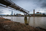 The Shard Building, Millennium Bridge and The Tate Modern Gallery on the River Thames at Low Tide.