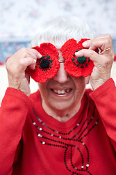 © Licensed to London News Pictures.  31/10/2013. OXFORDSHIRE, UK. Monica Stoter (80) holds up two knitted poppies at her home in East Hendred in Oxfordshire. She hand makes over 400 individual petals before knitting them together to form over 100 flowers. They are sold to family, friends and via Facebook raising hundreds of pounds for this year's poppy appeal.  Photo credit: Cliff Hide/LNP