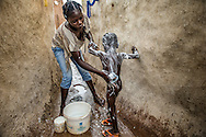 A young mother washes her child inside the family compound in the Ghanaian community of Yinduri. A newly installed water pump means the women and children don't have to travel far to haul water.