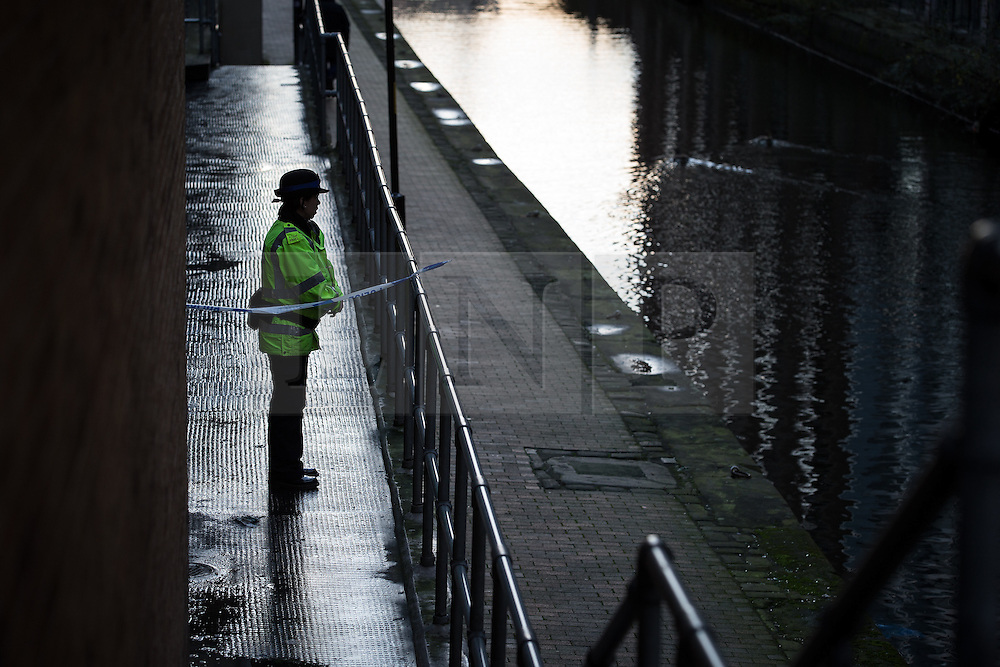 """© Licensed to London News Pictures . Manchester , UK . FILE PICTURE DATED 29/12/2013 of a PCSO standing behind police tape adjacent to the River Medlock off Oxford Road in Manchester City Centre . The search for a 17 year old from Stockport , who was last seen in the early hours of Saturday 28th December in Manchester City Centre following a night out with friends . Greater Manchester Police have issued a statement after suggestions that a number of deaths in and around Manchester's canals may be linked to a serial killer , named in local folklore as """" The Pusher """" . The statement said """" Absolutely no evidence whatsoever of foul play has been established """" . Photo credit : Joel Goodman/LNP"""