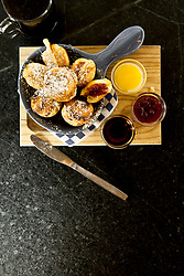 Aebleskiver with Jam Syrup and Butter in a Bowl next to them on a cutting board