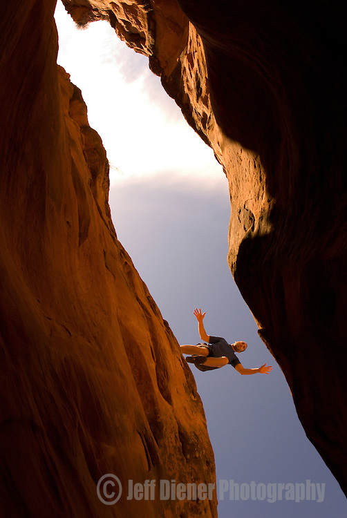 A young man leaps over a desert slot canyon in the Grand Staircase-Escalante National Monument, Utah.