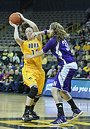 December 30, 2011: Iowa Hawkeyes center Morgan Johnson (12) tries to pass around Northwestern Wildcats forward/center Dannielle Diamant (31) during the NCAA women's basketball game between the Northwestern Wildcats and the Iowa Hawkeyes at Carver-Hawkeye Arena in Iowa City, Iowa on Wednesday, December 30, 2011.
