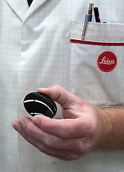 SOLMS, GERMANY - MAY-18-2009 - A technician inspects a piece of glass destined for the Leica 21mm F-1.4 lens, at yet another stage in the lens production process. (Photo © Jock Fistick)