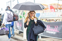 © Licensed to London News Pictures. 11/05/2019. Brighton, UK. A woman shelters from the rain in Brighton and Hove while she enjoys an ice cream. Colder weather and occasional rain show is hitting the seaside resort. Photo credit: Hugo Michiels/LNP