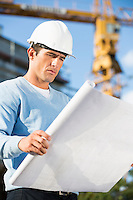 Male architect examining blueprint at construction site