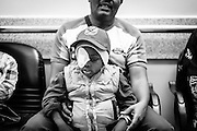 A boy from Uganda waiting with his father to be checked up after treatment. Children's Cancer Hospital, Cairo, Egypt.