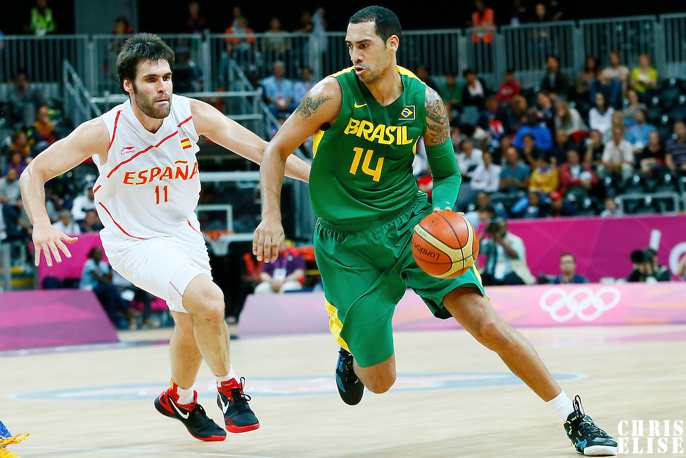 06 August 2012: Brazil Marquinhos Vieira Sousa drives past Fernando San Emeterio during 88-82 Team Brazil victory over Team Spain, during the men's basketball preliminary, at the Basketball Arena, in London, Great Britain.