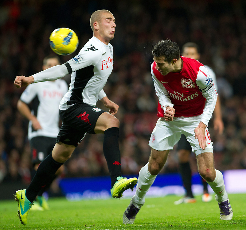 Arsenal's Robin van Persie heads a ball past Fulham's Pajtim Kasami during  their  English Premier League soccer match at the  Emirates stadium in London, Saturday, Nov. 26, 2011. (AP Photo/Bogdan Maran)