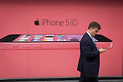 A man walks past a phone network supplier's ad for the Apple iPhone 5c