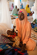 Karima Moussa, 25, holding Hassana, one of her five children, who is severely malnourished at the Save The Children malnutrition clinic at the Aguie hospital in the Maradi region of southern Niger. Located in the Western Sahel, the landlocked country suffers from chronic malnutrition and food insecurity caused by climate related drought and erratic rainy seasons, inadequate arable land, one of the highest demographic growth rates in the world, poor social and sanitary living conditions and widespread poverty. Food insecurity affects children under five and women disproportionately, especially in rural areas. Aguie, Niger. 15/07/2017.