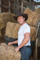 sexy cowboy working in a hay barn