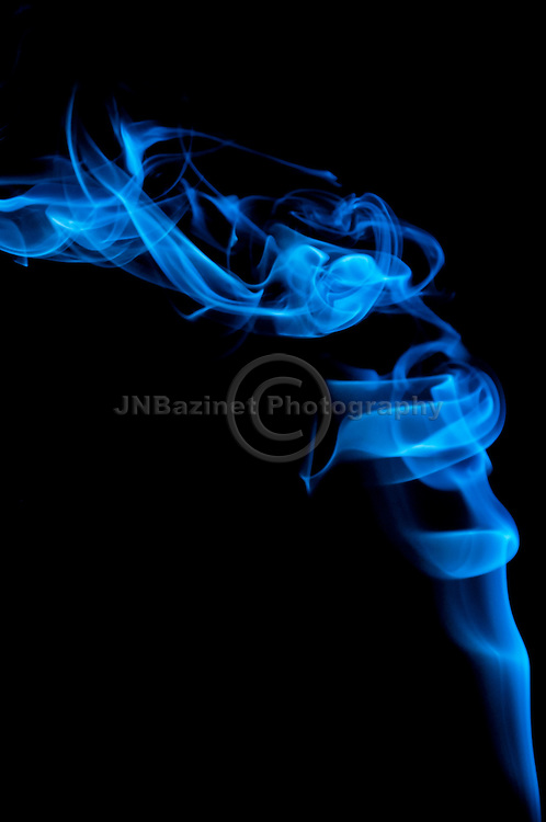 Two small birds nestled in a swirl of rising smoke