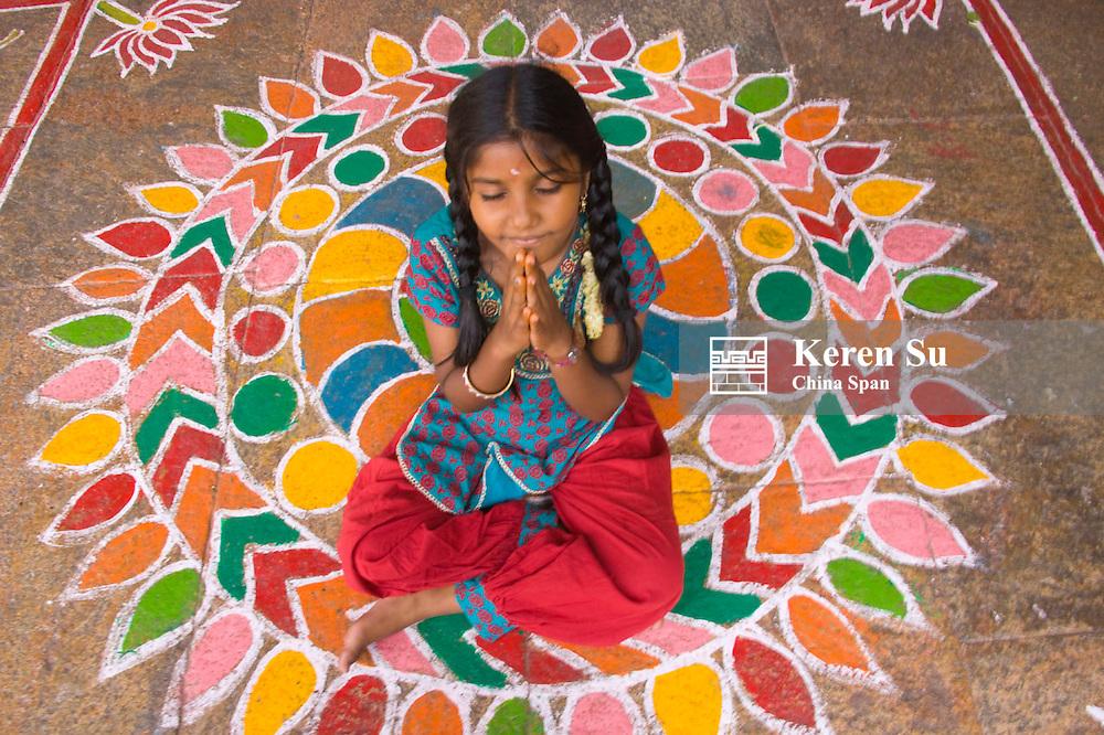Little girl praying on Hindu Mandala paintings, Sree Meenakshi Temple complex, Madurai, Tamil Nadu State, India