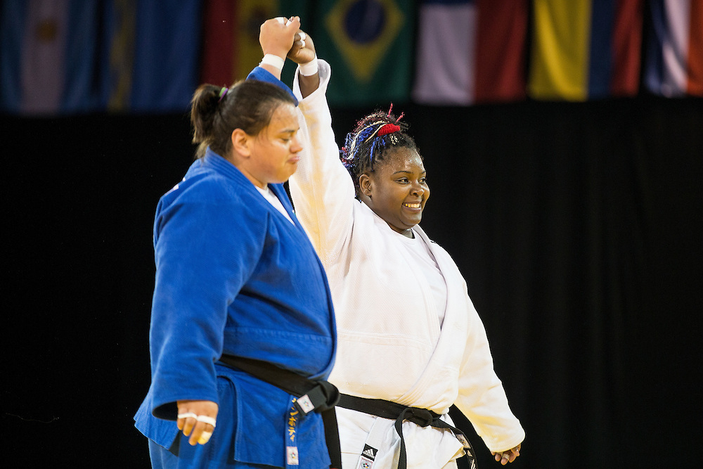 Idalys Ortiz (R) of Cuba raises the arm of Vanessa Zambotti of Mexico after defeating her to win the gold medal in the women's judo +78kg class at the 2015 Pan American Games in Toronto, Canada, July 14,  2015.  AFP PHOTO/GEOFF ROBINS