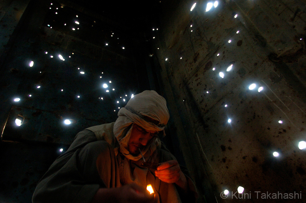 5/28/05 Kabul, Afghanistan.A man lights up for heroin in an abandon container near a cemetery in Old City section of Kabul. Tribune photo by Kuni Takahashi