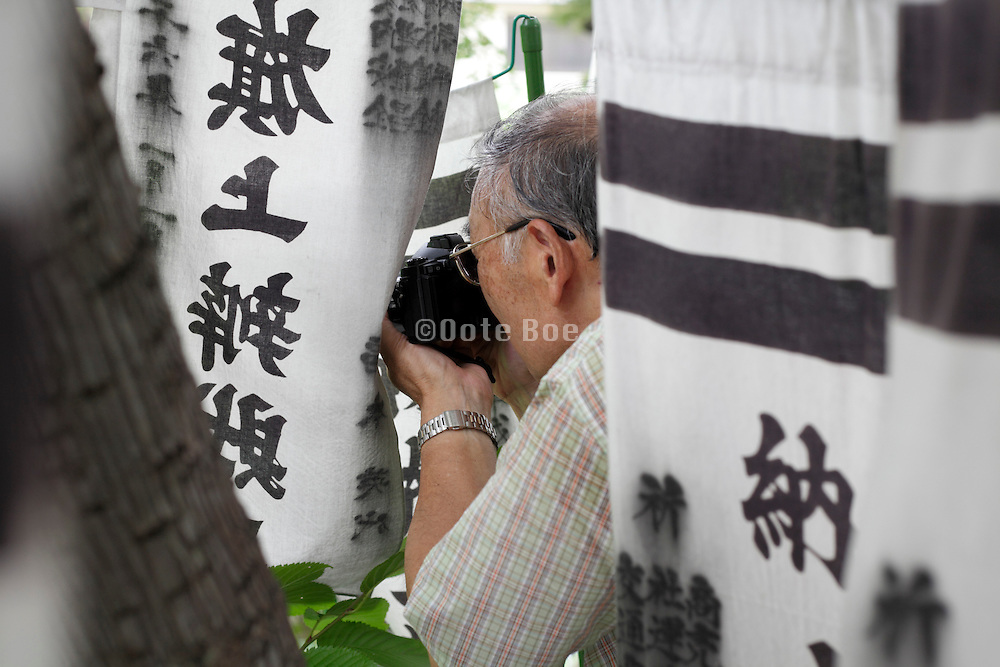 senior man taking pictures of flowers