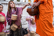 "11 MARCH 2013 - LUANG PRABANG, LAOS:  A woman drops a serving of sticky rice into a monk's alms bowl during the tak bat in Luang Prabang. The ""Tak Bat"" is a daily ritual in most of Laos (and other Theravada Buddhist countries like Thailand and Cambodia). Monks leave their temples at dawn and walk silently through the streets and people put rice and other foodstuffs into their alms bowls. Luang Prabang, in northern Laos, is particularly well known for the morning ""tak bat"" because of the large number temples and monks in the city. Most mornings hundreds of monks go out to collect alms from people.   PHOTO BY JACK KURTZ"