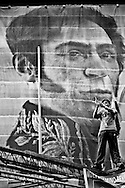Caracas - Venezuela. Outside of Venezuelan Congress a supporter plays a trumpet in front of a massive banner of Simon Bolivar, to celebrate the election of Nicolas Maduro for the presidency.