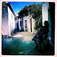 Kreta, Kroustas , 24 juli 2013.<br /> <br /> Een straatje in het bergdorpje Kroustas even ten Zuiden van Kritsa in het Noord Oosten van Kreta.<br /> Summer holiday on the Greek island of Crete. Streetview. Woman resting.