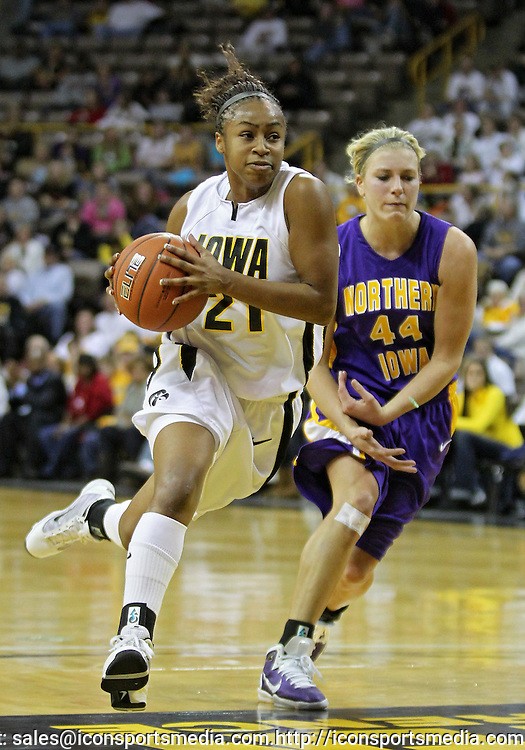 December 22 2010: Iowa guard Kachine Alexander (21) drives past Northern Iowa guard/forward Erin Brocka (44) during the first half of an NCAA college basketball game at Carver-Hawkeye Arena in Iowa City, Iowa on December 22, 2010. Iowa defeated Northern Iowa 75-64.
