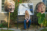 "Bellmore, New York, USA. November 2, 2016. EILEEN FUSCALDO, a Donald Trump Supporter, sits in her front yard on a bench seat with large pictures of Hillary Clinton's head on sticks, and ""Back the Blue"" police badge sign behind her, some of many in her front yard Halloween display for the Republican presidential candidate, D. J. Trump, and against Democratic one, H. R. Clinton."