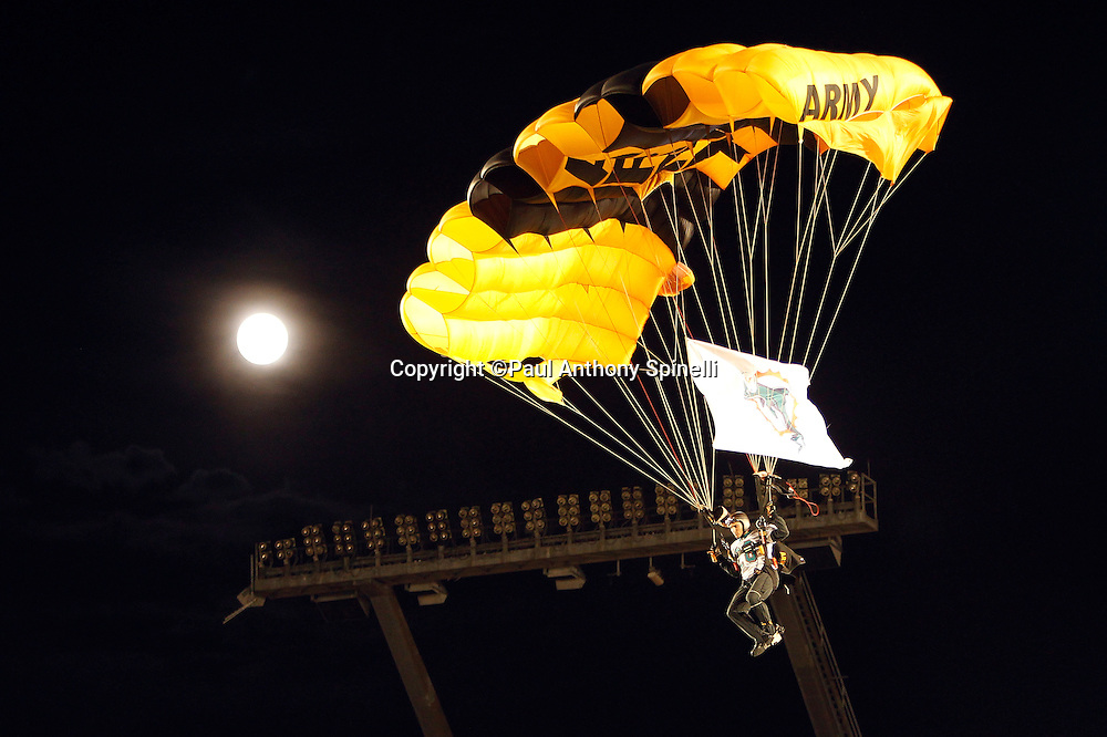 A member of the U.S. Army parachute team the Golden Knights parachutes into the stadium while the background shows a full moon during the Miami Dolphins NFL week 1 football game against the New England Patriots on Monday, September 12, 2011 in Miami Gardens, Florida. The Patriots won the game 38-24. ©Paul Anthony Spinelli