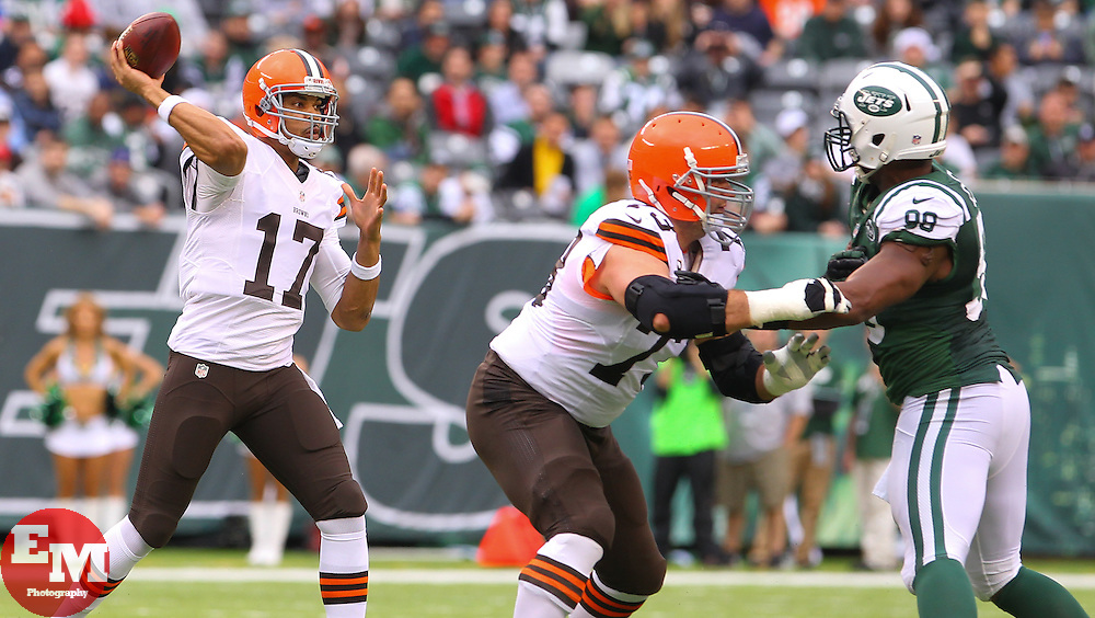 Dec 22, 2013; East Rutherford, NJ, USA; Cleveland Browns quarterback Jason Campbell (17) throws a pass while New York Jets outside linebacker Quinton Coples (98) rushes during the first half at MetLife Stadium.