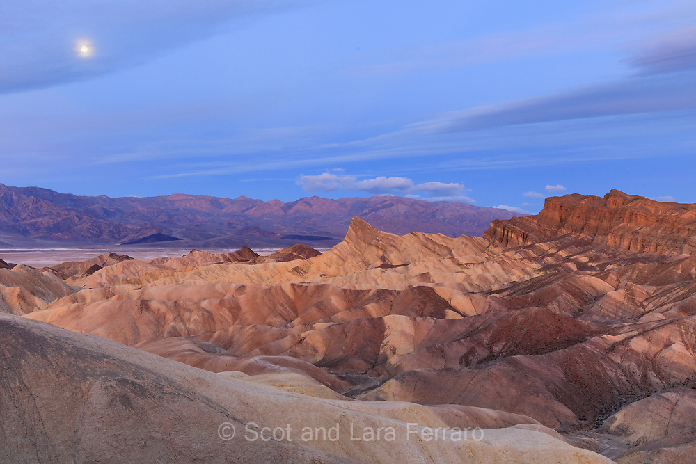 The predawn light at Zabriskie Point in Death Valley with the moon setting in the background.