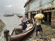 08 NOVEMBER 2014 - SITTWE, RAKHINE, MYANMAR:  Unloading rice from a small boat near the rice market in Sittwe. Sittwe is a small town in the Myanmar state of Rakhine, on the Bay of Bengal.  PHOTO BY JACK KURTZ
