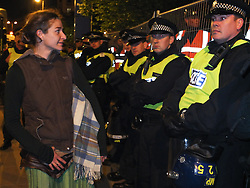 © licensed to London News Pictures. London, UK. 14/07/12. An activist who says she was a resident of the camp looks though lines of police and bailiffs towards the remaining tents. Enforcement officers clear the remaining 'Occupy' protest camp in London's Finsbury Square during the early hours of this morning after Islington Council won a High Court battle over the site. Photo credit: Jules Mattsson/LNP