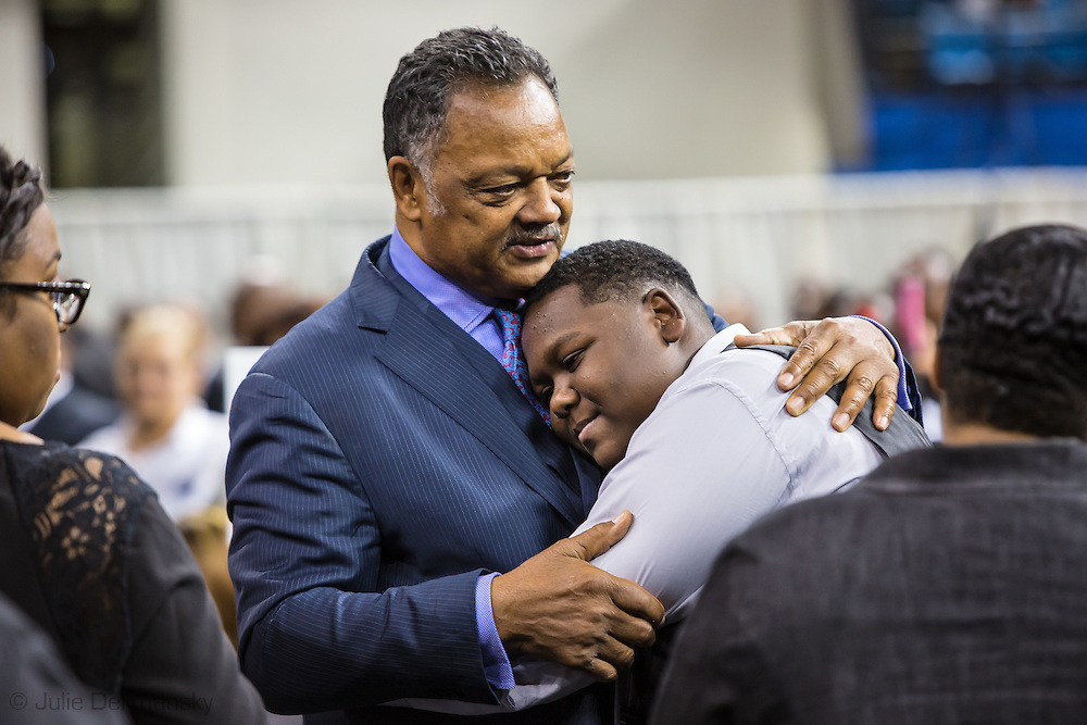"""Rev. Jesse Jackson gives Cameron Sterling, Alton Sterling's son a hug at <br /> Alton Sterling's funeral. The funeral was held at  Southern University's F.G. Clark Activity Center in Baton Rouge. Over a thousand people attended religious leaders including  Rev. Jesse Jackosn, Al Sharpton politicians, family members and friends friends.The Rev. Jesse Jackson told those at Alton Sterling's funeral """"Stop the violence, save the children. Stop the violence, save the nation.""""""""For those of you who are listening here and around the world, our strongest weapons are not guns and violence, it's the righteousness of our cause"""" and that,""""Unearned suffering is redemptive. There is power in innocent blood. If the killing of Alton Sterling would have been in a shootout or a drug bust or robbery, we would not be here today."""""""