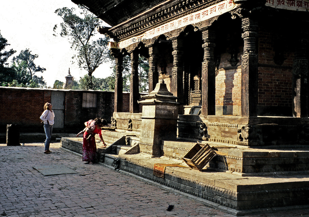 Nepali woman in a sari, baby tied to her back, makes an offering at an 18th century temple in Kathmandu, while a British young woman nearby studies the Newari wood carving of its colonnade and roof struts.