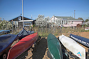 Bungalow chalets and canoes. Small fishing and sailing hamlet of Felixstowe Ferry at the mouth of the River Deben, Suffolk, England