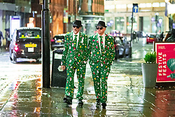"""© Licensed to London News Pictures . 21/12/2018 . Manchester , UK . Two men wear matching Christmas suits , inspired by the Blues Brothers . Revellers out in Manchester City Centre overnight during """" Mad Friday """" , named for historically being one of the busiest nights of the year for the emergency services in the UK . Photo credit : Joel Goodman/LNP"""