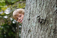 Portrait of boy (5-6) peeking from behind tree smiling