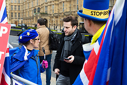 Watched by Steve Bray, the top hat wearing leader of SODEM, Bild journalist Philip Fabian speaks with pro-EU campaigner Sylvia outside the Houses of Parliament in London. London, January 14 2019.