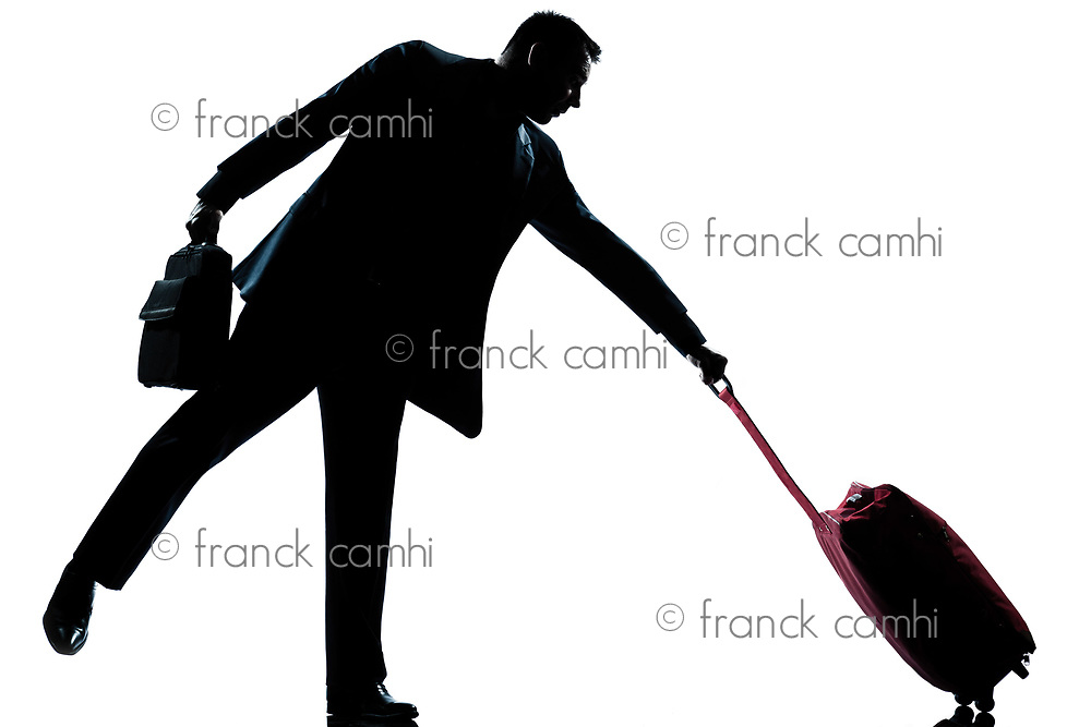 one caucasian man with his suitcase pulling him full length silhouette in studio isolated white background