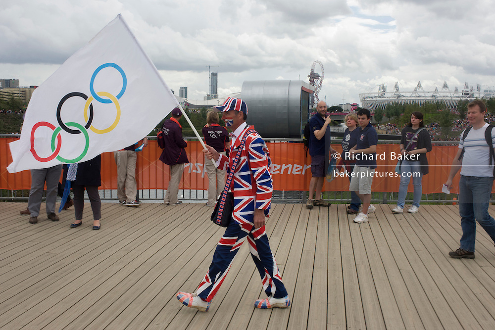 An eccentric Brit sports fan marches towards the Velodrome in the Olympic Park during the London 2012 Olympics. In the background is the main stadium and giant screen showing live coverage of selected Olympic events for crowds lining grass banks. Dressed in a union jack suit and carrying the IOC logo on a flag, he strides along a boadwalk. This land was transformed to become a 2.5 Sq Km sporting complex, once industrial businesses and now the venue of eight venues including the main arena, Aquatics Centre and Velodrome plus the athletes' Olympic Village. After the Olympics, the park is to be known as Queen Elizabeth Olympic Park.